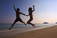 Silhouette of couple jumping Stock Photo