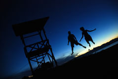 Silhouette of couple jumping in the air Royalty Free Stock Images