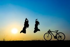 Silhouette couple jumping. Silhouette of couple jumping on sunset sky with bicycle on the prairie at yellow evening horizon sea yellow sunset heaven background Royalty Free Stock Photos