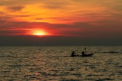 Silhouette of couple are kayaking in the sea at sunset. Kayak in the tropical sea at sunset. Romantic couple travel on summer. Vacation. Adventure activities of royalty free stock images
