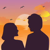 Silhouette of a couple kissing against a sunset sky.  Royalty Free Stock Photography