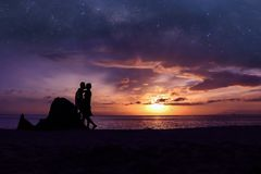 Silhouette couple kissing on the beach with million stars galaxy and purple sky. Sunrise background royalty free stock images