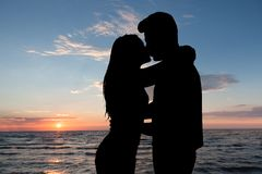 Silhouette of couple kissing at beach during sunset. Silhouette Of Couple Kissing In Front Of Sea At Beach During Sunset Royalty Free Stock Images