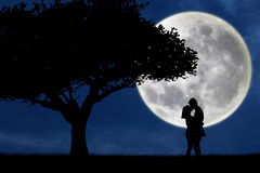 Silhouette of couple kissing on blue full moon Stock Images