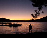Silhouette of couple kissing on the lake at sunset Stock Photos