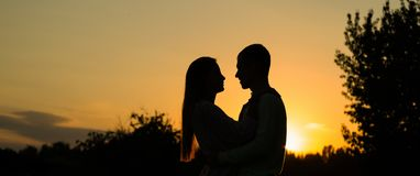 Silhouette couple kissing over sunset background, Profiles of romantic couple looking at each other on background of sunset stock photography