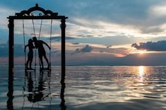 Silhouette of Couple Kissing Standing on Swing in Calm Sea during Sunset Royalty Free Stock Photo