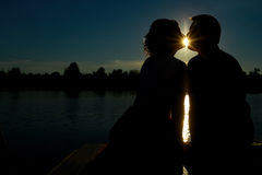 Silhouette of couple kissing at sunset at lake.  Royalty Free Stock Image