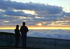 Silhouette couple looking at the beautiful sunrise on the top of Royalty Free Stock Images