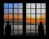 Silhouette of a couple looking through window stock photos