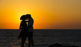 Silhouette of a couple in love on the beach at sunset. Love story.Man and a women on the beach.Beautiful couple in the sunlight.Silhouettes kissing against the Stock Image