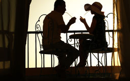 Silhouette of couple in love drink a drink Stock Images