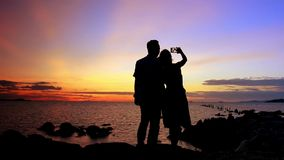 Silhouette couple in love taking self-portrait on Royalty Free Stock Photo