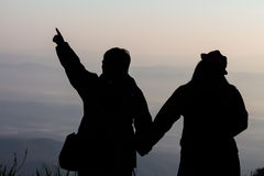 Silhouette of a Couple and love travel. Sky clouded sunset in mountain Royalty Free Stock Image