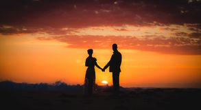 Silhouette of couple lovers, bride and groom holding hands durin stock photography