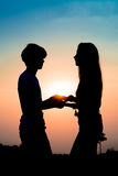 Silhouette couple. Silhouette of a couple lovers standing holding hand at the sunset time and they gaze into each other's eyes. Have a beauty pink and blue sky Stock Images