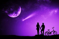 Silhouette couple man and woman holding hand moon night watching a meteor. With a purple proton mixed media bike royalty free stock image