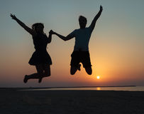 Silhouette of a couple - man and woman jumping on the beach Royalty Free Stock Image