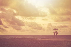 Silhouette of couple people or tourist standing on the beach in. Silhouette of couple people or tourist standing on the tropical beach in sunset time. Warm tone Royalty Free Stock Images