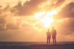 Silhouette of couple people or tourist standing on the beach in. Silhouette of couple people or tourist standing on the tropical beach in sunset time. Warm tone Stock Photography