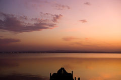 Silhouette of a couple on pier. Silhouette of a kissing couple on pier at sunset Stock Photo
