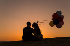 Silhouette of a couple playing with balloons at sunset Royalty Free Stock Photography