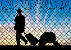 Silhouette of a couple of refugees. Concept of the refugees. Silhouette of a couple of refugees near the border fence at sunset Stock Photography