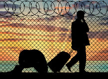Silhouette of a couple of refugees. Concept of the refugees. Silhouette of a couple of refugees near the border fence at sunset Royalty Free Stock Image