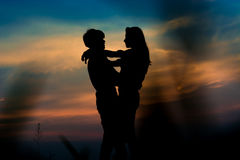 Silhouette couple. Silhouette of romantic couple stand hugging and gaze into each other's eyes on meadow at the sunset time . Have a beauty blue sky Stock Photo