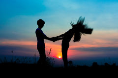 Silhouette couple. Silhouette of romantic couple at the sunset time on meadow. Have a beauty pink and blue sky Stock Photos