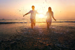 Silhouette of couple running to the sea Stock Photos