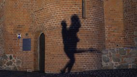 Silhouette of a couple in the shadow actively dancing on a stone wall.