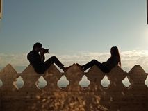 Silhouette of couple sit on wall and take photo each other. Royalty Free Stock Photography