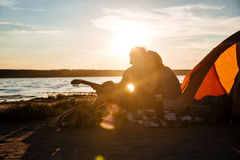 Silhouette of couple sitting near touristic tent and hugging Royalty Free Stock Photos