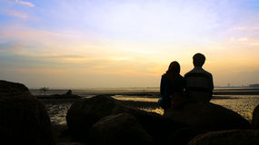 Silhouette of couple sitting on the rock looking at the sun Royalty Free Stock Photos
