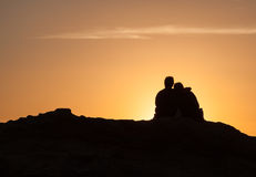 Silhouette of Couple sitting on a rock at sunset Royalty Free Stock Images