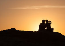 Silhouette of Couple sitting on a rock at sunset Royalty Free Stock Photos