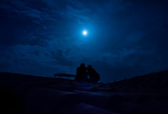 Silhouette of couple sitting on a roof under a full moon Stock Photography