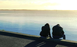 Silhouette of a couple sitting at the seaside in the sunset, calm sea Royalty Free Stock Photos
