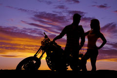 Silhouette couple stand by motorcycle Stock Photos