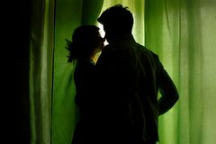 Silhouette of couple standing at green curtains at window and hu. Gging Royalty Free Stock Image