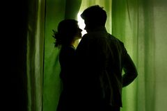 Silhouette of couple standing at green curtains at window and hu. Gging Royalty Free Stock Photos