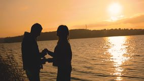 Silhouette of couple, stands at the lake with sunset glow, kisses and caresses. Slowly stock footage