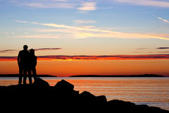 Silhouette of couple in sunset. Silhouette of couple holding together with sunset on sea Stock Image