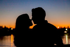 Silhouette of Couple at Sunset by Lake. A romantic scene of a silhouetted couple in front of a lake at sunset. They lean in for a kiss but their lips aren't yet Stock Photo