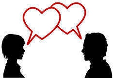 Silhouette couple talk love hearts. A couple of lovers talk love in heart speech bubbles at valentines or any time Stock Photography