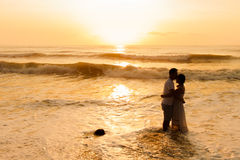Silhouette of couple about to kiss on beach. At sunrise stock photo