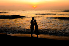 Silhouette of couple about to kiss on beach. At sunrise royalty free stock image