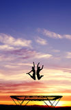 Silhouette of couple on trampoline Stock Photo