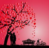 Silhouette of couple under a love tree in the spring season Stock Photos